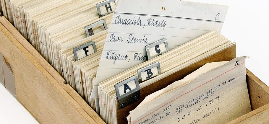Countless faded index cards are stacked one behind the other, meticulously arranged in alphabetical order.