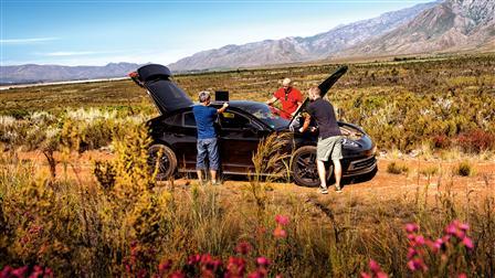 Porsche engineers discuss measurement results next to the new Porsche Panamera